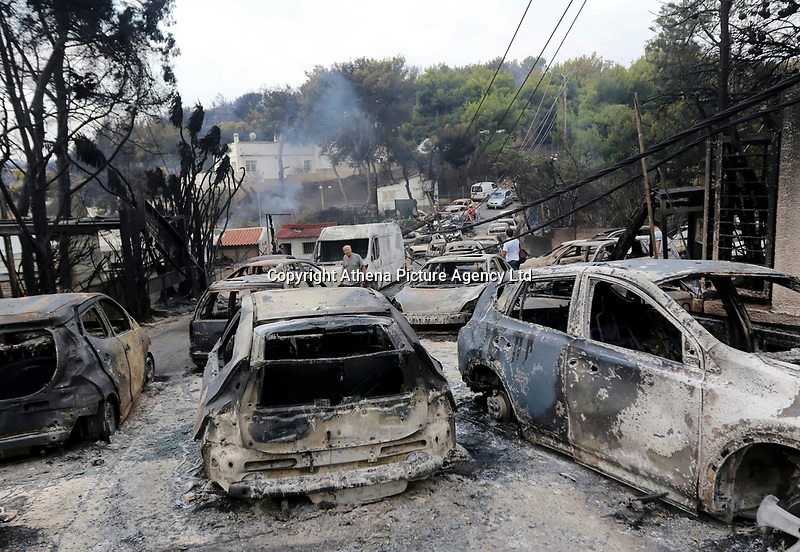 Pictured: Dozens of cars destroyed by the blaze in the Mati area, Kokkino Limanaki near Rafina, Greece. Tuesday 24 July 2018<br /> Re: Deaths caused by wild forest fires throughout Greece.