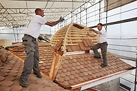 Switzerland. Geneva. Two laborers from the company Cerutti Toitures SA are working on a private house's new roof. Roofing and woodwork. 20.03.2014 © 2014 Didier Ruef