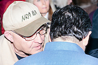 A man wearing a hat for the NRA-ILA, the lobbying arm of the National Rifle Association, whispers in the ear Texas senator and Republican presidential candidate Ted Cruz as he greets people after speaking at a town hall at The Alpine Grove banquet center in Hollis, New Hampshire.