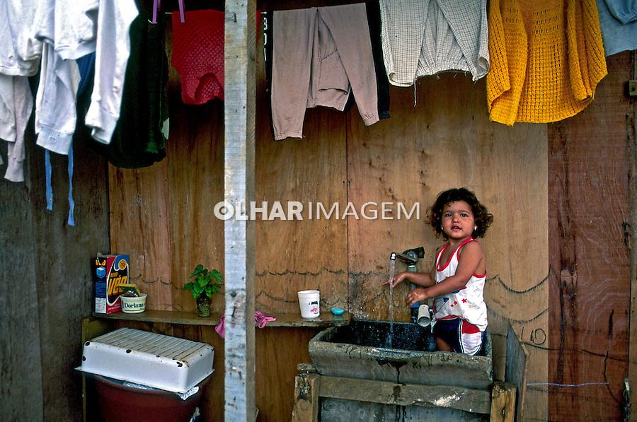 Criança no tanque, favela de Heliópolis. São Paulo. 1993.Foto de Juca Martins. Data:1993