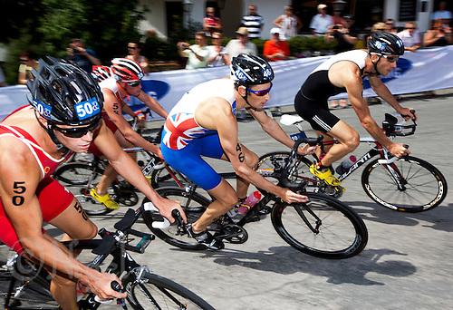 24 JUN 2012 - KITZBUEHEL, AUT - Stuart Hayes (GBR) of Great Britain (centre, in blue and white) on the bike during the elite men's 2012 World Triathlon Series round in Schwarzsee, Kitzbuehel, Austria (PHOTO (C) 2012 NIGEL FARROW)