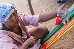"Young Wayuu indigenous woman in a Wayuu ""rancheria"", or rural village, weaving textiles on a loom, Uribia, La Guajira, Colombia.  Textile weaving is an important social tradition and source of income for women in Wayuu communities of northern Colombia."