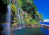 Beautiful waterfall reflects a rainbow in Hana, Maui.