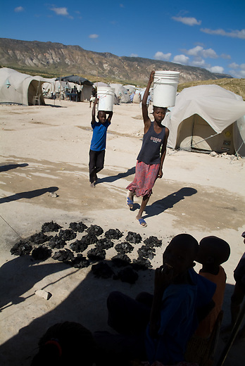 Jean Baptiste(10 years) and his sister Josephin come back to the shelter after getting freshwater from the water tank. Jean has to to a few times a day to get water for cleaning the tent, wash and cook the food, as well as taking a shower or washing cloths. In front of the tent are portions of charcoal which Jean and his family sells to other families in the camp. Charcoal is used for cooking in haiti because of very few people can affort the price of gas and it's installations.