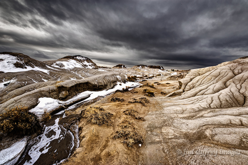 An eroded landscape under a stormy sky at Mesa de Cuba Badlands in the San Juan Basin of northwestern New Mexico.
