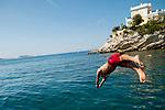 A boy dives off the rocks below Le Petit Nice Passedat, Marseille, 16.06.2011