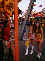 Dressed to be noticed in go-go boots and mini-dresses, young ladies at the LA County Fair in California exchange flirtatious smiles with a friendly carnie