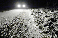 Snow on road with car headlights.