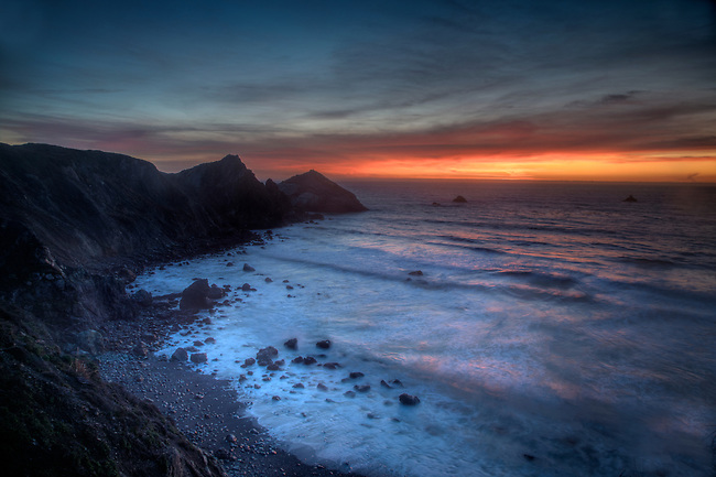 Waves crash along the coastline during sunset near San Simeon, California.