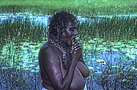Traditional Australian Aboriginal women killing a fresh water file snake the traditional way by gripping the snakes head with her teeth and the given it a sharp jerk to break the neck, Top End Northern Territory, Australia