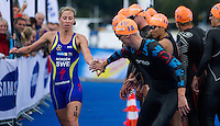 26 AUG 2012 - STOCKHOLM, SWE - Lisa Norden (SWE) of Sweden (left) tags team mate Per Wangel (SWE) during the 2012 ITU Mixed Relay Triathlon World Championships in Gamla Stan, Stockholm, Sweden (PHOTO (C) 2012 NIGEL FARROW)