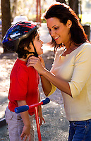 Mother clasps safety helmet on her son.