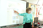 Education Elementary school Grade 2 female science specialist pointing at smart board with computer projection on it class not visible horizontal