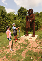 """SOUVENIR SNAPSHOT<br />Kelly (left) and Dan Santema stop Tuesday July 20 2021 to take pictures of """"Sassy,"""" a Sasquatch sculpture along the Razorback Greenway in Bentonville. The art piece was created in 2018 by Amanda Willshire of Colorado, reads an information panel by the sculpture. It is made mostly of bicycle chains. The Santemas are visiting the area from Austin, Texas to bicycle in Bentonville and play golf in Bella Vista. Go to nwaonline.com/210721Daily/ to see more photos. <br />(NWA Democrat-Gazette/Flip Putthoff)"""