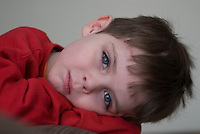 Five-year-old boy in a red sweatshirt  plays before the camera<br />