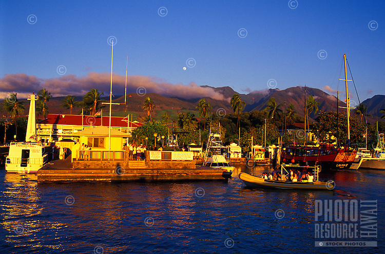 Tourists on a boat ride return to the loading dock with a view of the full moon over Lahaina Harbor and the West Maui Mountains. The harbor includes the Lahaina Lighthouse, the main loading dock, the Pioneer Inn and more.