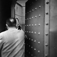 """Affaire de la """"Tournerie des drogueurs""""  JUIN 1961<br /> <br /> Devant l'entrée de la prison Saint-Michel. 3 juin 1961. Plan rapproché de la porte d'entrée de la prison, est entrouverte, un homme de dos tient la porte ; en arrière-plan on aperçoit le visage de Marie-Thérèse Davergne (accusée), porte un foulard et des lunettes noires. Cliché pris dans le cadre de l'affaire de la """"Tournerie des drogueurs"""" dont le procès s'est ouvert à Toulouse le 5 juin 1961. Observation: Affaire de la """"Tournerie des drogueurs"""" : Procès qui s'est ouvert aux assises de Toulouse le 5 juin 1961, sous la présidence de M. Gervais (conseiller doyen). Sur le banc des accusés se trouvent François Lopez, Raoul Berdier, Marie-Thérèse Davergne (Maïté) et d'autres malfaiteurs toulousains (Camille Ajestron, Henri Oustric, Raymond Peralo, Marcel Filiol, Paul Carrère, Charles Davant et François Borja). Outre les accusations pour association de malfaiteurs, ils comparaissent pour l'assassinat de Jean Lannelongue, propriétaire du Cabaret la Tournerie des Drogueurs (rue des Tourneurs) dans la nuit du 3 au 4 janvier 1959, au cours d'une tentative de racket."""