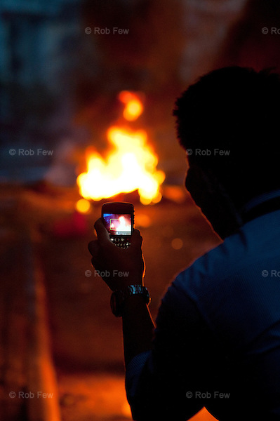 A protestor photographs burning tyres at Din Daeng.<br /> <br /> From March to May 2010, Red Shirt protestors occupied several sites in Bangkok in an attempt to oust the government, who they believed had come to power illegitimately. <br /> <br /> When the tanks finally rolled in, clearing away the last of the Red Shirts, more than 80 people had been killed and more than 2,000 injured.