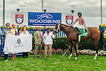 Conquest Typhoon(5) with Jockey Patrick Husbands aboard in the winners circle at the Summer Stakes at Woodbine Race Course in Toronto, Canada on September 13, 2014.