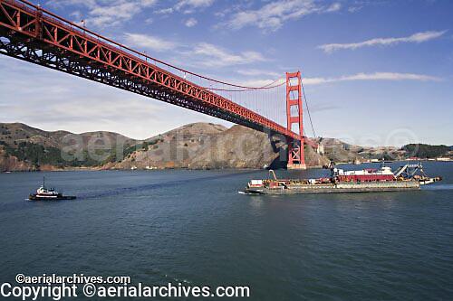 aerial photograph tug boat pulling loaded barge under Golden Gate bridge