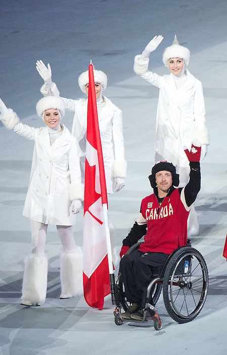 Sochi, RUSSIA - Mar 16 2014 - Joshua Dueck carries the Canadian into the Closing Ceremonies at the 2014 Paralympic Winter Games in Sochi, Russia.  (Photo: Matthew Murnaghan/Canadian Paralympic Committee)