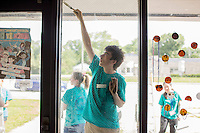 """Members paint the outside of an entryway during """"Circle the City with Service,"""" the Kiwanis Circle K International's 2015 Large Scale Service Project, on Wednesday, June 24, 2015, at the Friendship Westside Center for Excellence in Indianapolis. (Photo by James Brosher)"""