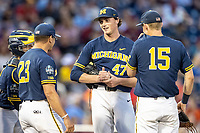 Michigan Wolverines pitcher Tommy Henry (47) talks with head coach Erik Bakich (23) on the mound during Game 6 of the NCAA College World Series against the Florida State Seminoles on June 17, 2019 at TD Ameritrade Park in Omaha, Nebraska. Michigan defeated Florida State 2-0. (Andrew Woolley/Four Seam Images)