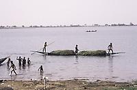 Un groupe de garçons à moitié nus riant dans l'eau près du rivage - Ségou, Mali - novembre-décembre 1993<br /> <br /> 1993 - A group of half-naked boys laughing in the water by the shore. A piroque (prahu) with three men with a punt tree transports a load of grass along the river