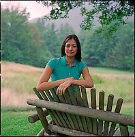 Woman, leaning over bench, looking at camera<br />