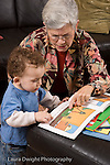 2 year old toddler boy at home with grandmother interaction read to from picture book language development both child and grandmother pointing to illustration vertical she takes care of him when parents work