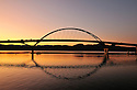 The graceful arch of the newly constructed Champlain Bridge reflected in the waters of Lake Champlain at sunset, Addison, Vermont.