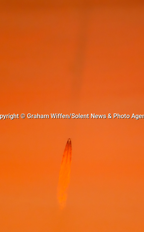Pictured: UFO? The mysterious craft spotted flying near Milford-on-Sea, Hants last night.<br /> <br /> A mysterious craft spotted flying through the skies last night left confused Britons arguing over what it might be - with some suggesting 'aliens'.  The 'UFO' could be seen flying vertically in orange sky at 8.45pm on Wednesday on the British coastline, leaving a long trail behind it before it rolled and 'disappeared' out of sight.<br /> <br /> The peculiar sight baffled people, with a group of astrophotographers guessing that it was a 'rocket taking off', a 'fighter aircraft' or a 'typhoon jet'.  Some even claimed it could be aliens - or Dr Who in a Tardis.  Retired salesman Graham Wiffen, who captured the shots from coastal village Milford-on-Sea, Hants, as he looked out across Dorset, thought he was witnessing a rocket.  SEE OUR COPY FOR DETAILS.<br /> <br /> Please byline: Graham Wiffen/Solent News<br /> <br /> © Graham Wiffen/Solent News & Photo Agency<br /> UK +44 (0) 2380 458800
