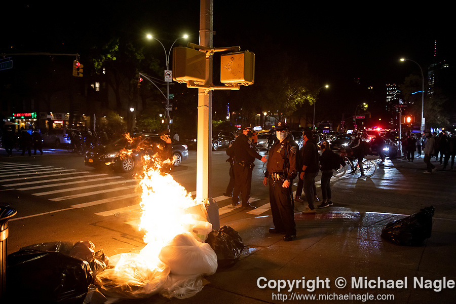 NYPD police officers stand next to a fire during a protest demanding every vote cast be counted in the 2020 presidential election between U.S. President Donald Trump and former Vice President Joe Biden on November 4, 2020 in New York City.  Photograph by Michael Nagle