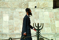 An Orthodox Jew walks near the Western Wall (also called the Wailing Wall) in Jerusalem. The Western Wall is one of the holiest shrines of the Jewish faith, a place where Jews go to pray and to tuck handwritten prayers into the cracks of the wall. Jerusal