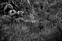 Nukak kids pass through a dense jungle around their refugee camp close to San Jose del Guaviare, Colombia, 3 September 2009. The Nukak Maku people, nomadic hunter-gatherers from Amazonia, were violently driven out of the jungle by the Colombian guerilla and paramilitary squads. Now, roughly cut off their original tribal lifestyle, they stuck between worlds. They learn from the (mainly Christian) aid workers to use clothes, to listen to the radio, to beg for money. Although their digestion suffer, they love to eat sweets, cookies and other western food. They have hunted out all the animals around and now there is nothing left for them. Nukak can not return to the jungle, their world has already passed through an irreversible change.