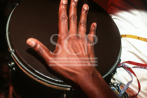 Rio de Janeiro, Brazil. Man playing a tom-tom drum with his hand.