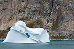 An iceberg with a hole in Greenland's Prins Christian Sound.