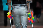 © Joel Goodman - 07973 332324 . 26/08/2016 . Manchester , UK . A man with rainbow garlands around his crutches in Manchcester's Gay Village for 2016 Manchester Gay Pride Big Weekend . Photo credit : Joel Goodman
