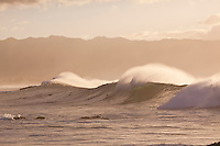 Surfers riding big waves at sunset with Mount Kaala in the background at Waimea Bay, North Shore, Oahu