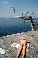 Switzerland. Zoug. Summer season. A young man dives into the lake of Zoug, while an other sleeps on a wooden pontoon under the sun. © 1989 Didier Ruef