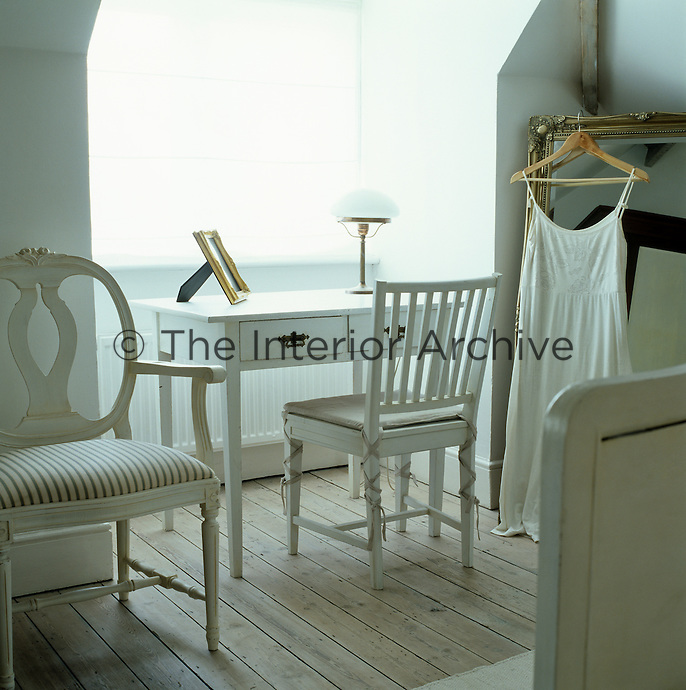 A white wooden desk and a Gustavian-style chair have been placed infront of the window in this attic bedroom