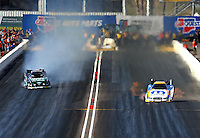 Feb 21, 2014; Chandler, AZ, USA; NHRA funny car driver Matt Hagan (right) races down track as John Force smokes the tires during qualifying for the Carquest Auto Parts Nationals at Wild Horse Pass Motorsports Park. Mandatory Credit: Mark J. Rebilas-USA TODAY Sports