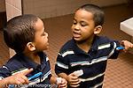 Education Preschool 3-4 year olds health and hygiene boy brushing his teeth in bathroom looking at his reflection in mirror horizontal