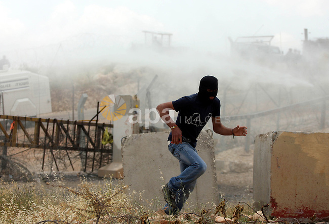 """A Palestinian protestor run for cover from tear gas canisters during a protest against Israel's controversial separation barrier and to mark the 63th anniversary of """"Nakba"""" (catastrophe) on May 13, 2011in the West Bank village of Bilin. Nakba means """"catastrophe"""" in reference to the birth of the state of Israel 63 years ago in British-mandate Palestine, which led to the displacement of hundreds of thousands of Palestinians who either fled or were driven out of their homes during the 1948 war over Israel's creation. Photo by Issam Rimawi"""