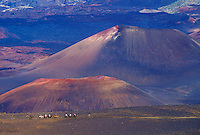 Haleakala National Park, Maui. Horseback riders wind past cinder cones in dormant volcano crater on sliding sands trail, also known as Keoneheehee