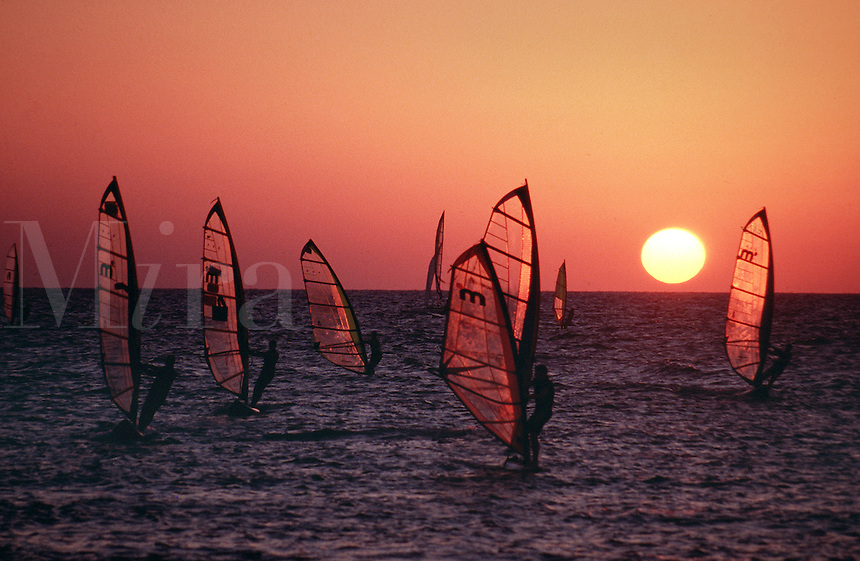 Dramatic crimson sunset with windsurfers in silhouette on the Mediterranean Sea. Israel..
