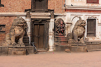 Bhaktapur, Nepal.  Lions Guarding Entrance to Palace, Durbar Square.  The smaller stone sculpture to the right of the door shows Narasimha, Man-lion Avatar of Vishnu, Victorious over the Demon Hiranyakasipu.