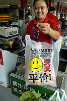 Checkout counter of US retail giant Wal Mart flagship 'Supercenter' store in China's richest city, Shenzhen, with shopping bag decorated with a smiley face and slogan about permanent discount prices..01 Nov 2004