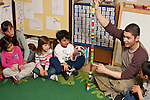Education Preschool Headstart 3-4 year olds circle time young male teacher leading activity cube tower representing days in school