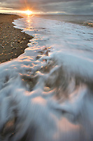 Coastal landscape of waves washing upon the sandy beach along Norton Sound, Bering Sea, Nome, in western arctic Alaska.